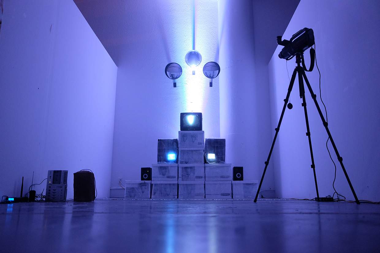 Banker's boxes, television sets, security mirrors, handmade adobe brick, radio transmitter, theater-light, VHS camera, speakers, and audio recording of footsteps on reflective silver