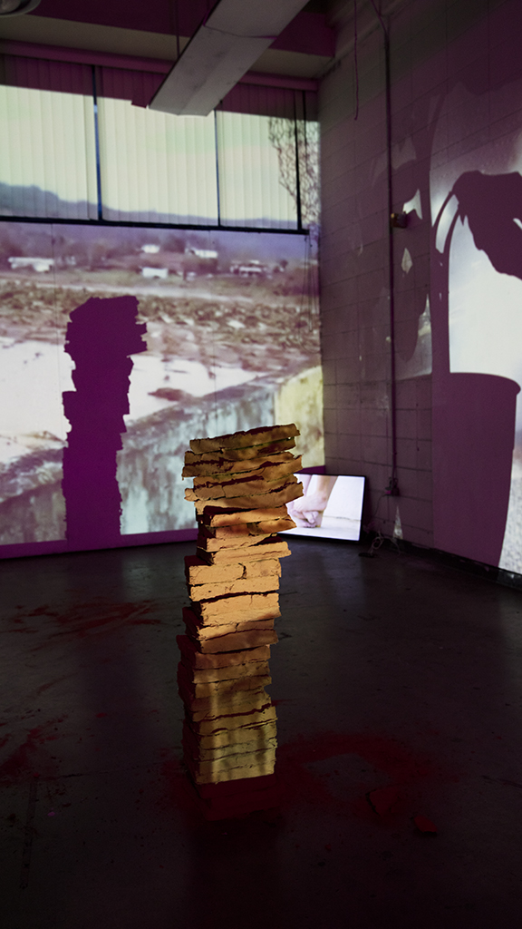 tiles stacked 4ft tall Self portrait made with dirt from Puerto Rico, migrated to U.S. and placed in obstructing view of video projection.
