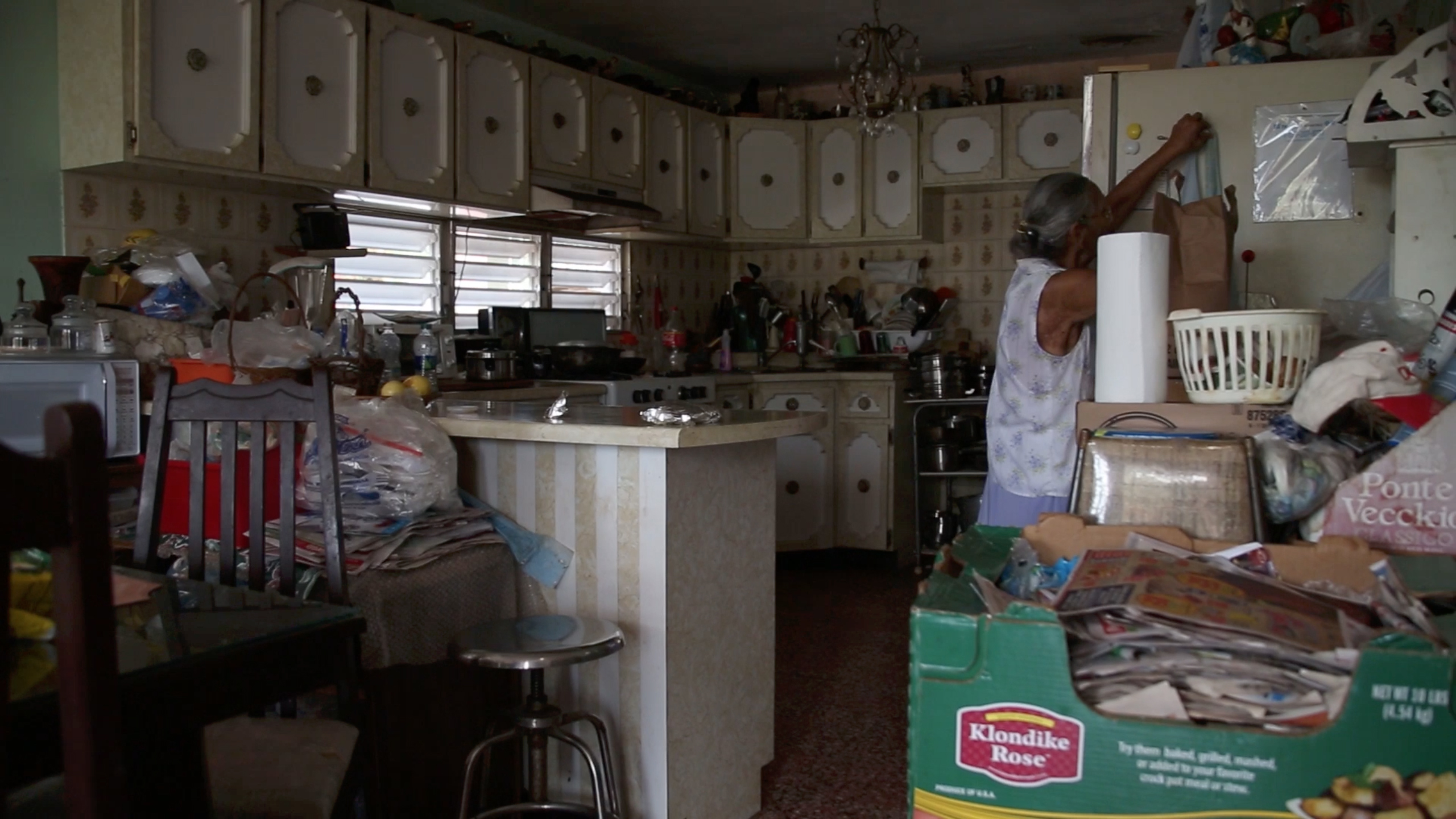 Video, Looped in multiple monitors 360 visual of grandparents living room, environmental and appropriated audio from youtube blog teaching Americans how to buy land in Puerto Rico